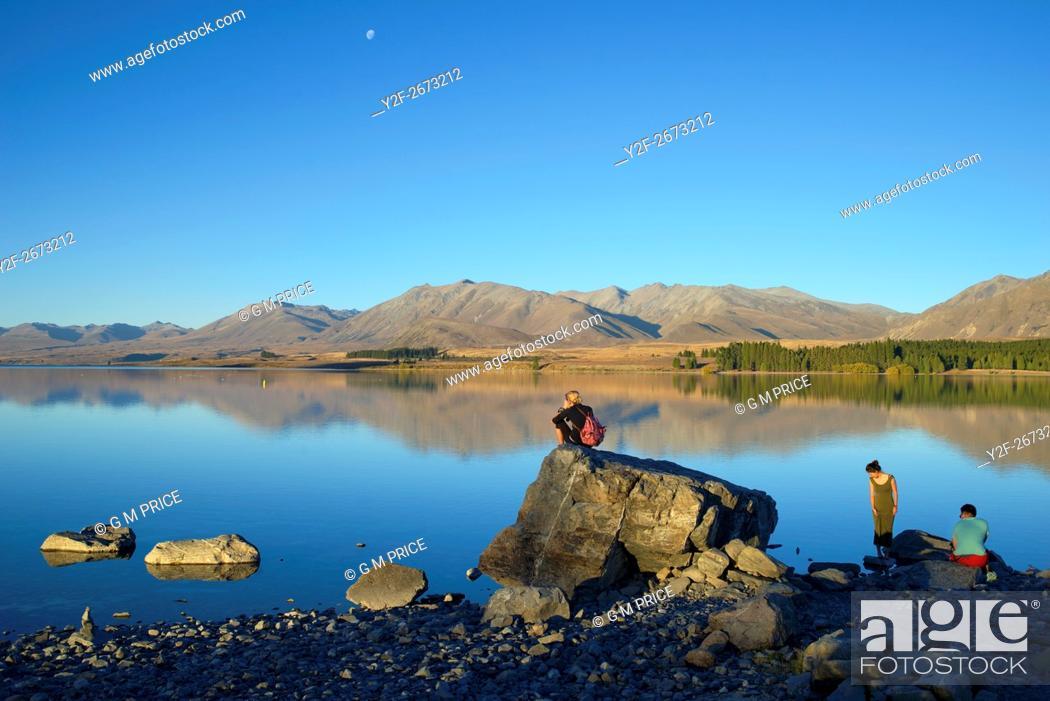 Imagen: travellers sit by Lake Tekapo, New Zealand.
