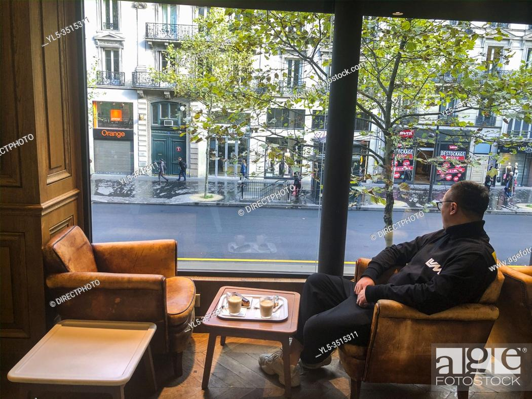 Stock Photo: Paris, France, Chinese Tourist Relaxing, Sitting Alone at Table, Inside Window, French Cafe in Latin Quarter, .