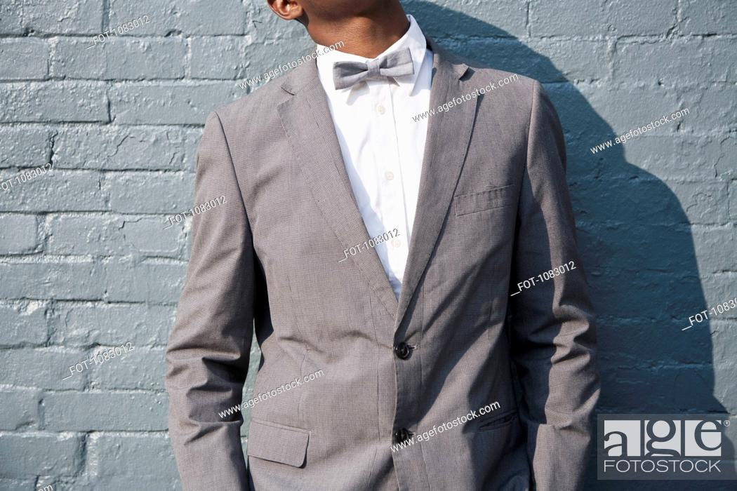 Stock Photo: A man wearing a bow tie and suit, midsection.