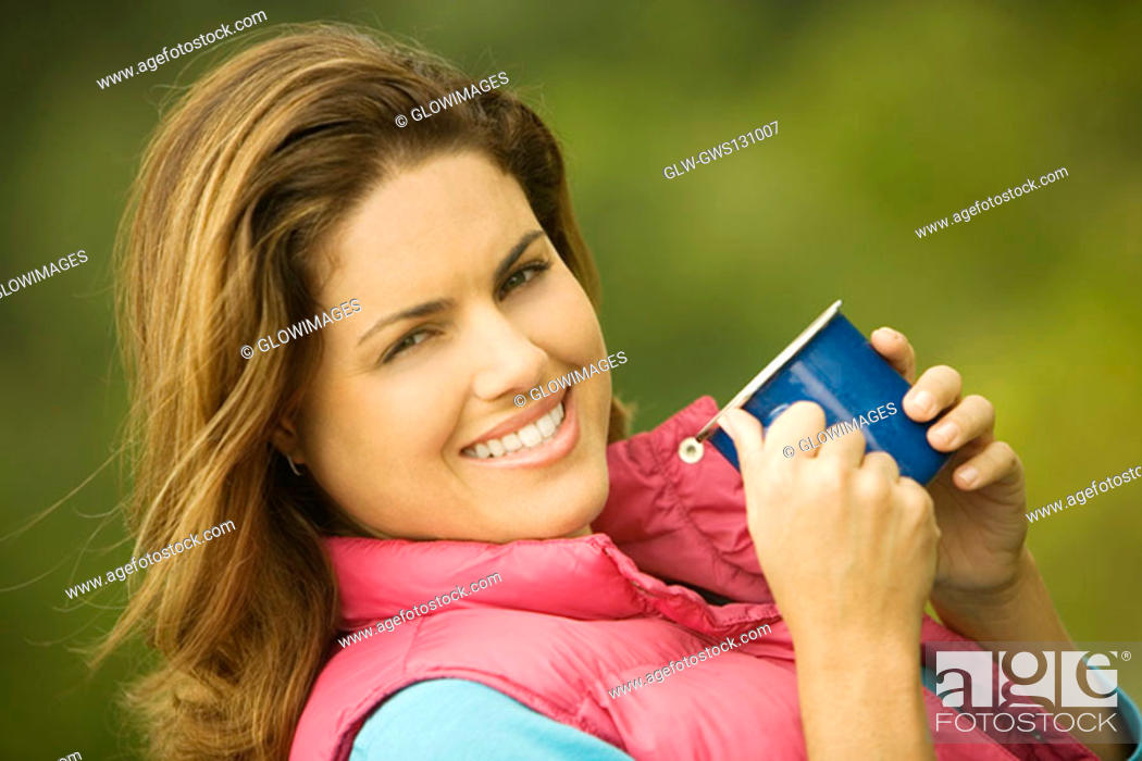Stock Photo: Portrait of a young woman holding a mug.