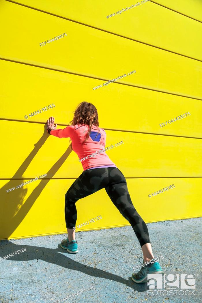 Stock Photo: young woman stretching on a yellow wall before running.