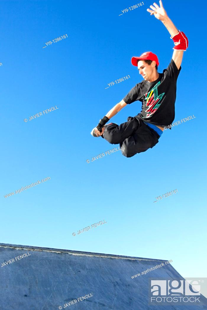 Stock Photo: Young man jumping in mid air wearing inline skates.