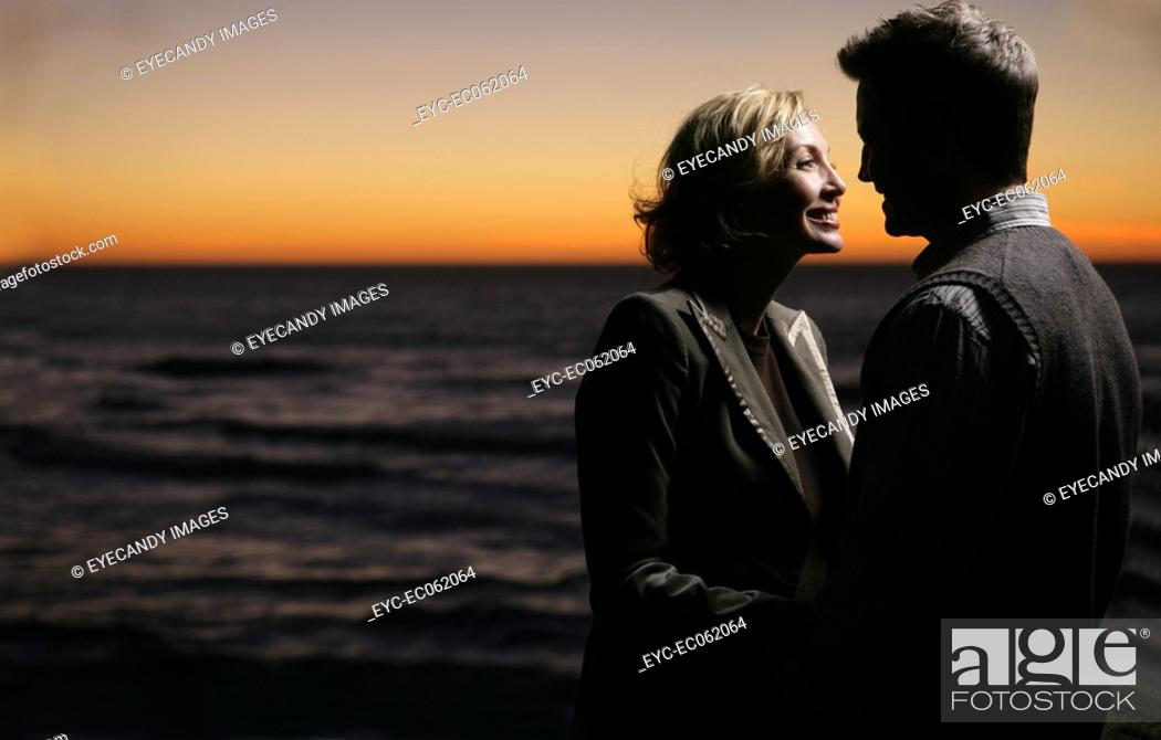 Stock Photo: Mature couple embracing at the beach at night.