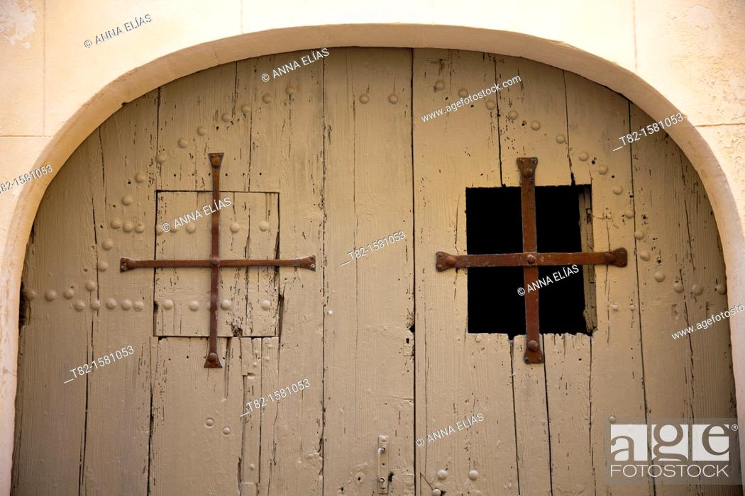 Stock Photo: detail round door and two windows with cross-shaped grille, Fontvieille, France.