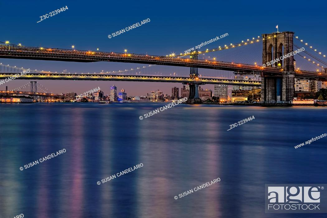 Stock Photo: Evening view of New York City's iconic Brooklyn, Manhattan and Williamsburg Bridges. Viewed from the historic area of South Street Seaport in lower Manhattan in.