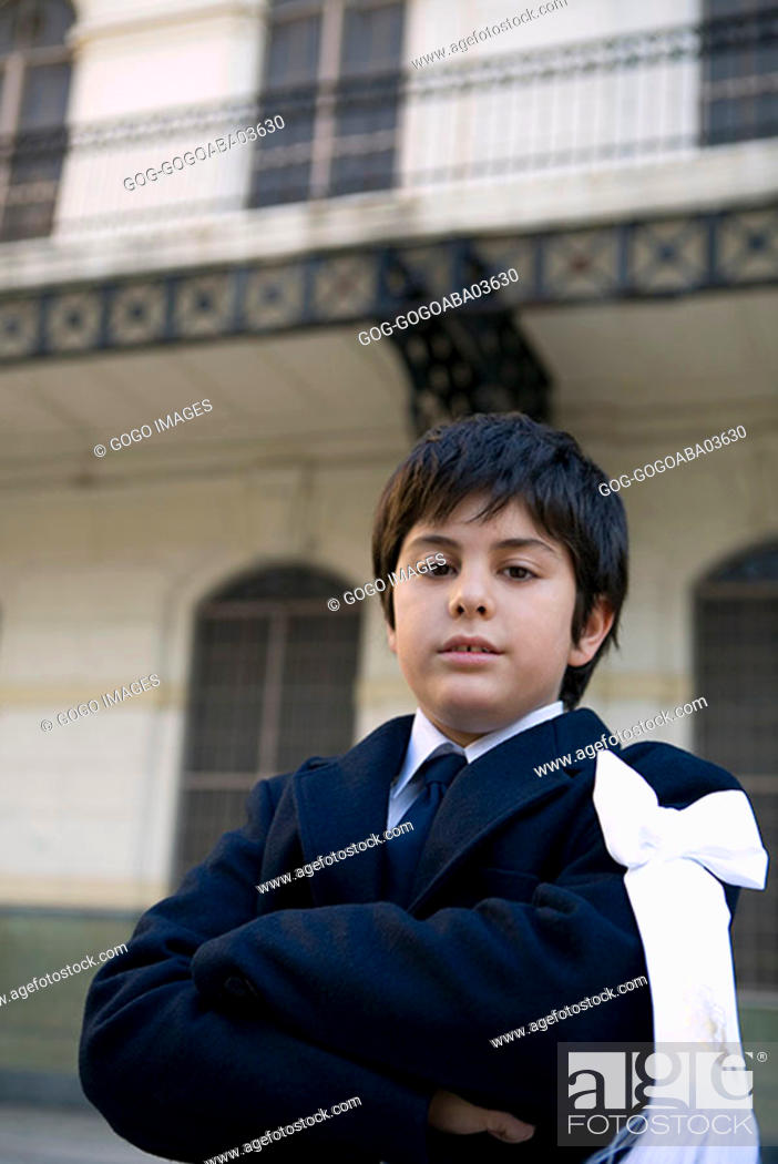 Stock Photo: Young boy wearing a suit in courtyard.