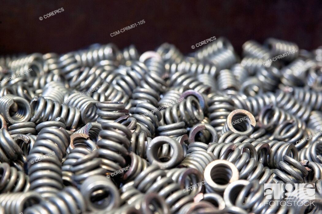 Stock Photo: Many chamfered compression springs in a box.