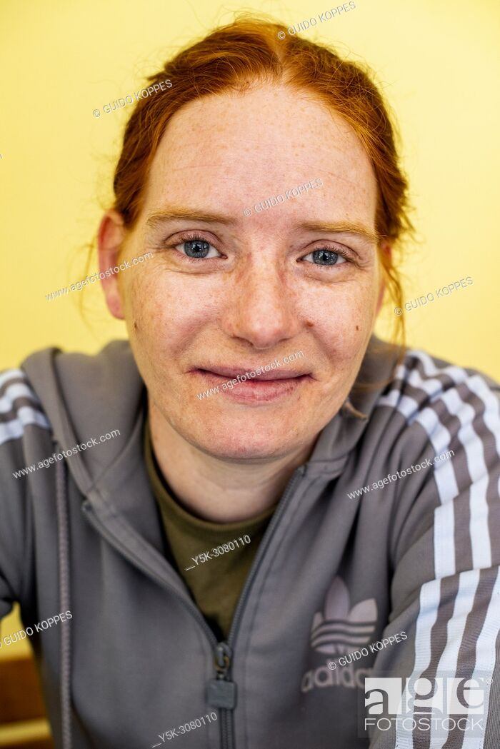Photo de stock: Tilburg, Netherlands. Studio-portrait of a cigarette smoking, redhaired woman wearing a branded shirt against a yellow background.
