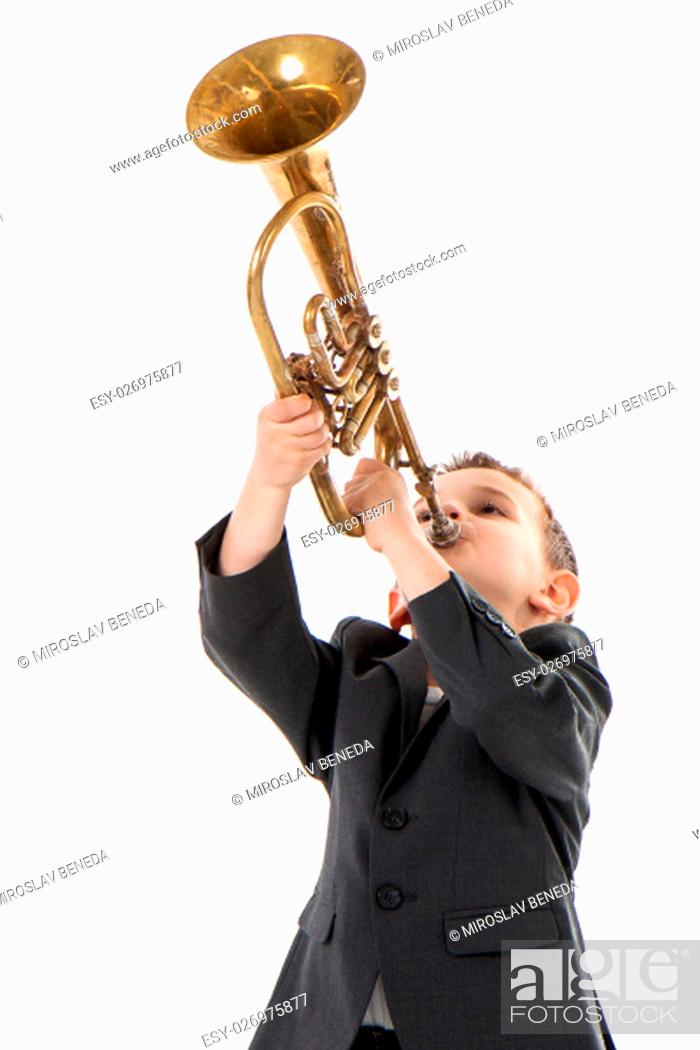 Stock Photo: young boy blowing into a trumpet against white background.
