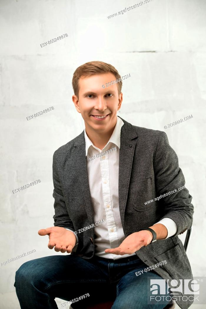 Stock Photo: Young fair handsome man wearing white shirt, jacket and jeans sitting on a chair with a gentle smile portrait against white wall.