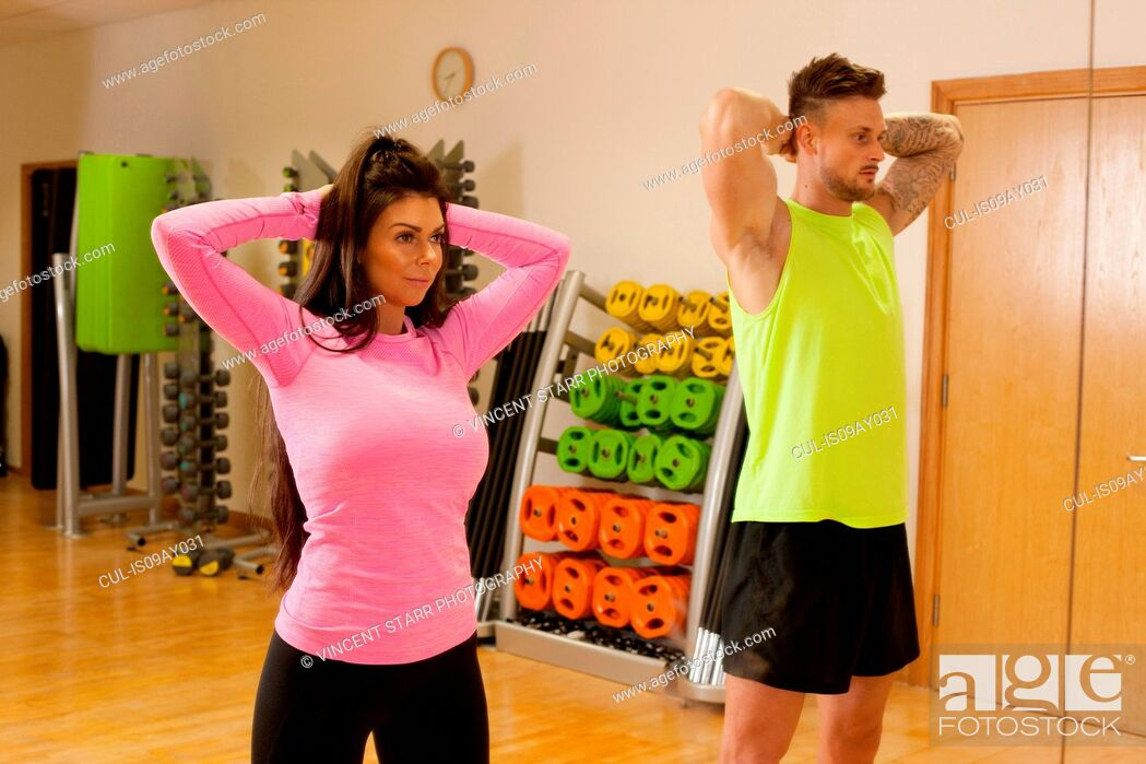 Imagen: Man and woman in gym standing with hands behind head.