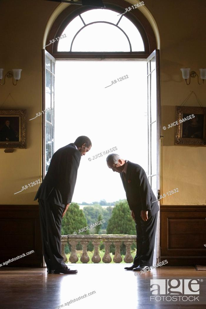 Stock Photo: Two businessmen looking down by open window, side view.