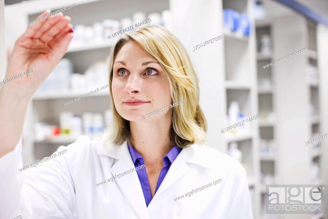 Stock Photo: Pharmacist holding pill.