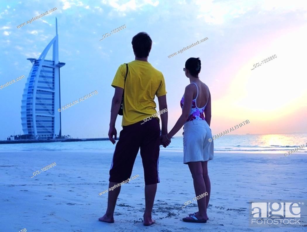 Stock Photo: Western couple looking at Burj Al Arab hotel from the beach, Dubai, UAE.