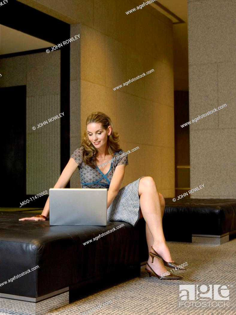Stock Photo: Woman using laptop in lobby.