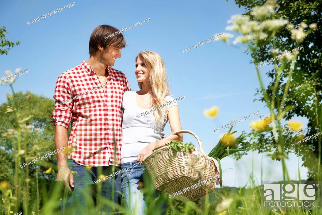 Stock Photo: Germany, Cologne, Young couple with picnic basket in meadow, smiling.