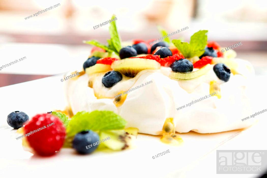 Stock Photo: Pavlova, a home made cake from layers of meringue, whipped cream, and fresh berries.