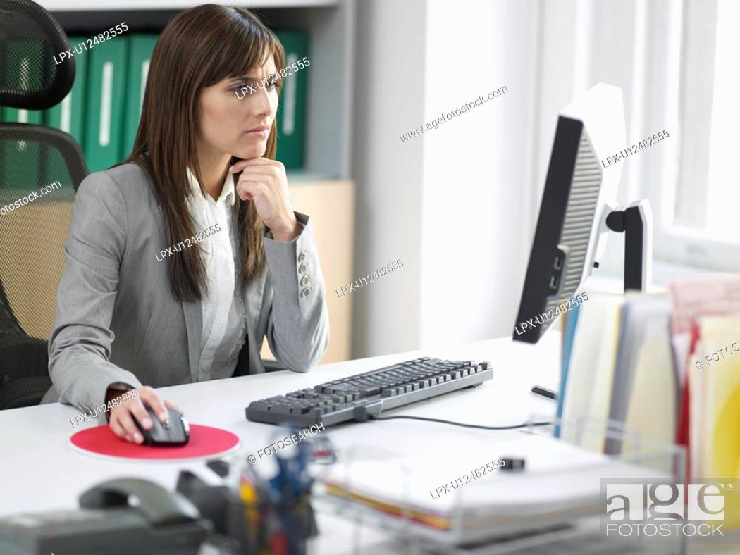 Stock Photo: Worried Female Office Worker at Desk.