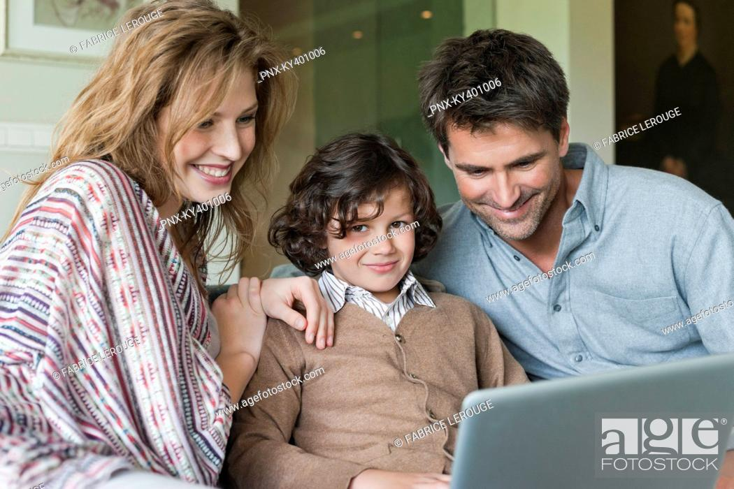 Stock Photo: Boy using a laptop with his parents at home.