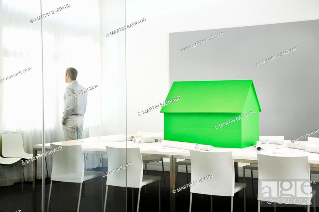 Stock Photo: Small green model house on conference table.