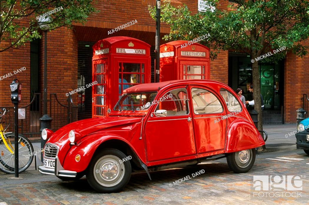 Stock Photo: England - London - red vintage car parked by telephone booths.