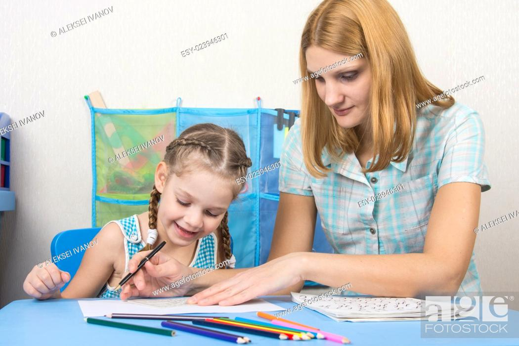 Stock Photo: A five-year girl is engaged with adult young beautiful girl sitting at the children table at home.