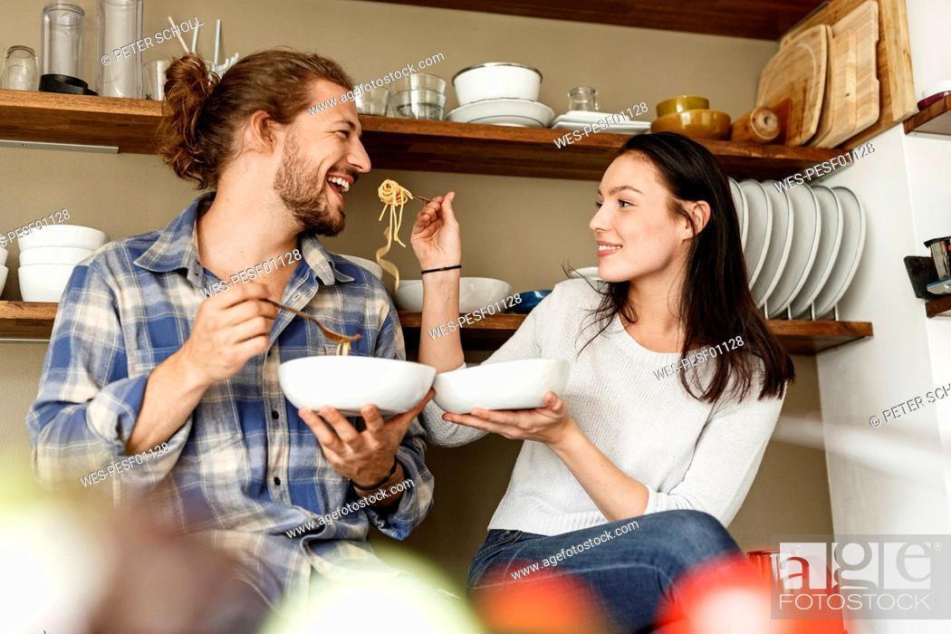 Stock Photo: Happy couple sitting in kitchen, eating spaghetti.