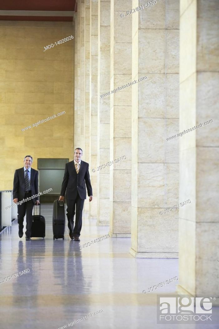 Stock Photo: Two business men pulling luggage in airport lobby.
