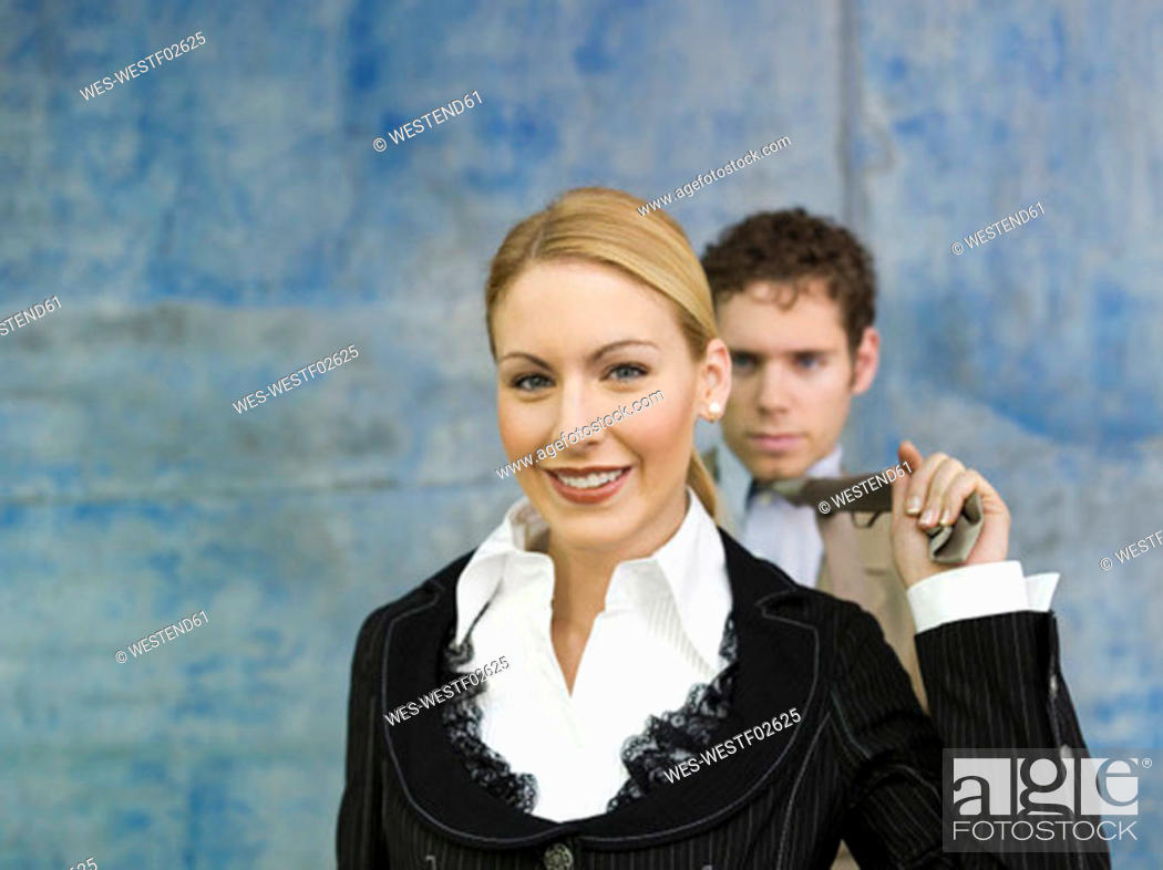 Stock Photo: Businesswoman pulling businessman's tie, smiling.