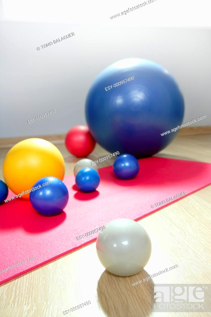 Stock Photo: balls stability and toning pilates sport gym on red yoga mat.