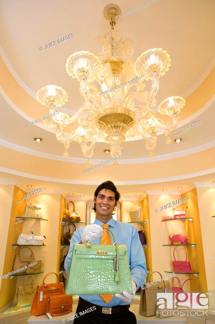 Stock Photo: Salesman displaying purse.
