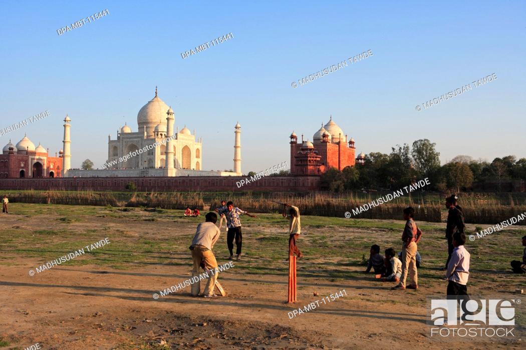 Stock Photo: Children playing cricket at Taj Mahal Seventh Wonders of World on south bank of Yamuna river , Agra , Uttar Pradesh , India UNESCO World Heritage Site.