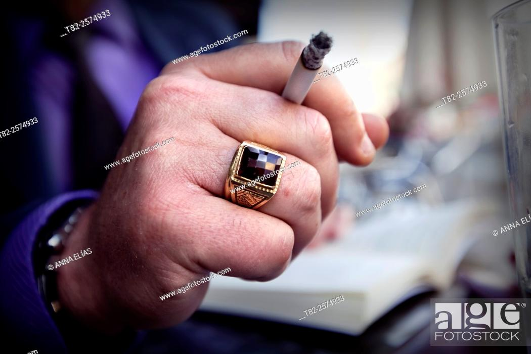 Stock Photo: close-up of male hand with ring holding a cigarette in the street.