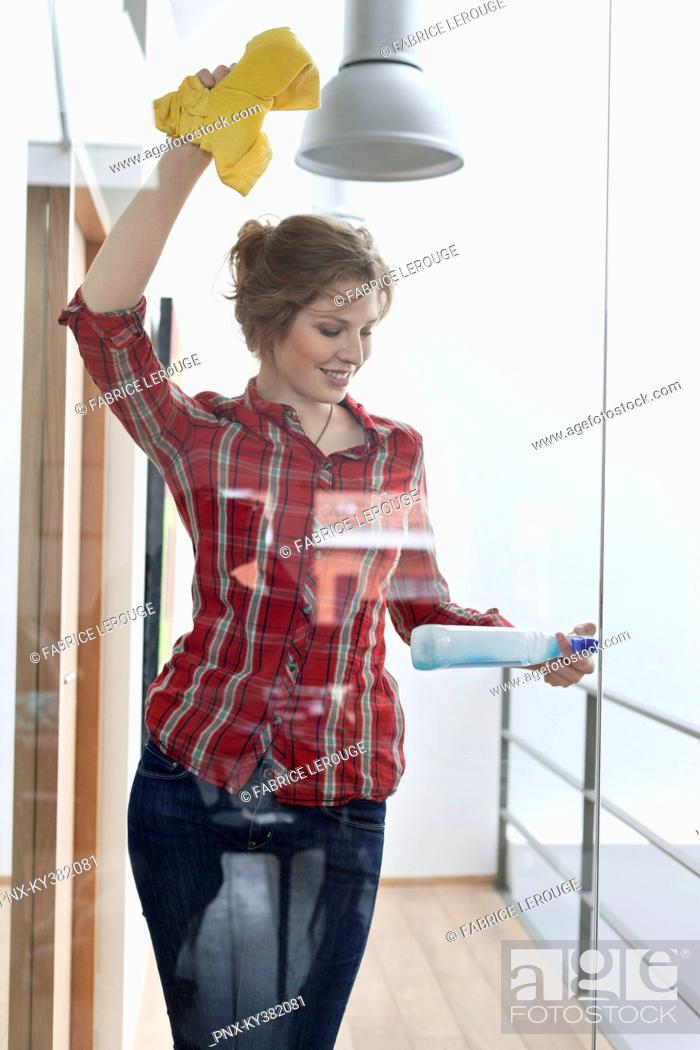 Stock Photo: Woman cleaning glass door.