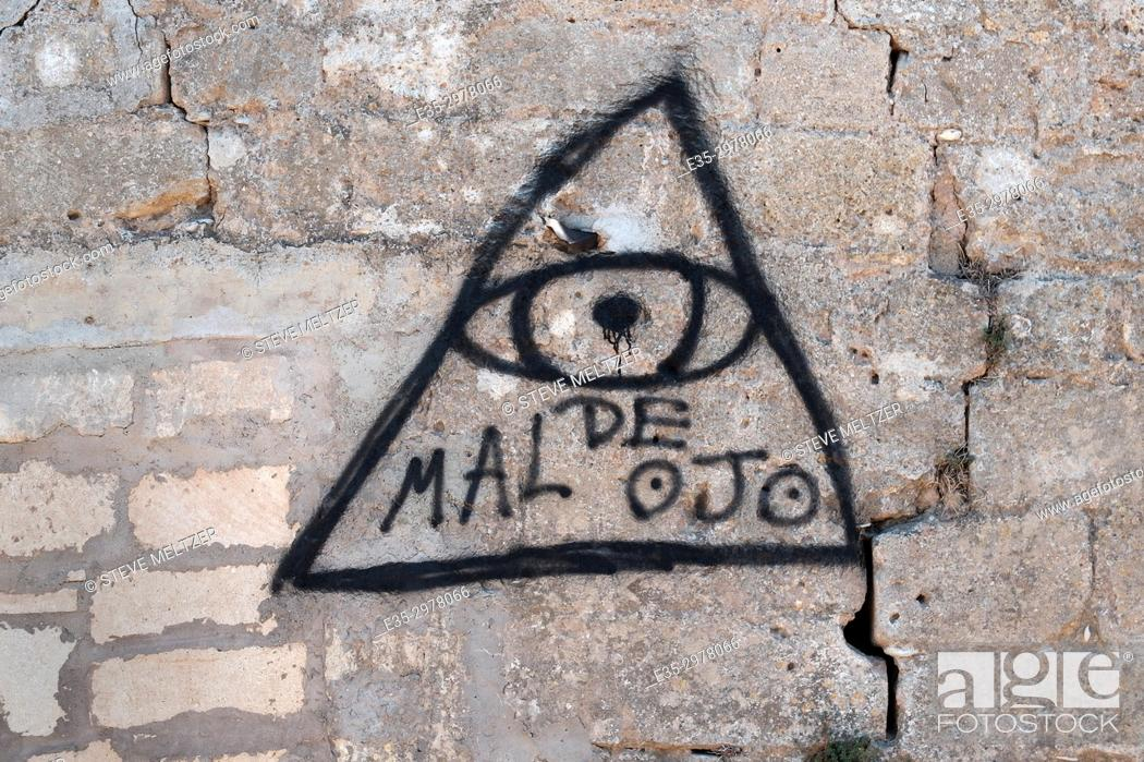 """Stock Photo: A graffiti """"""""evil eye"""""""" painted by a gypsy on a wall in the South of France."""