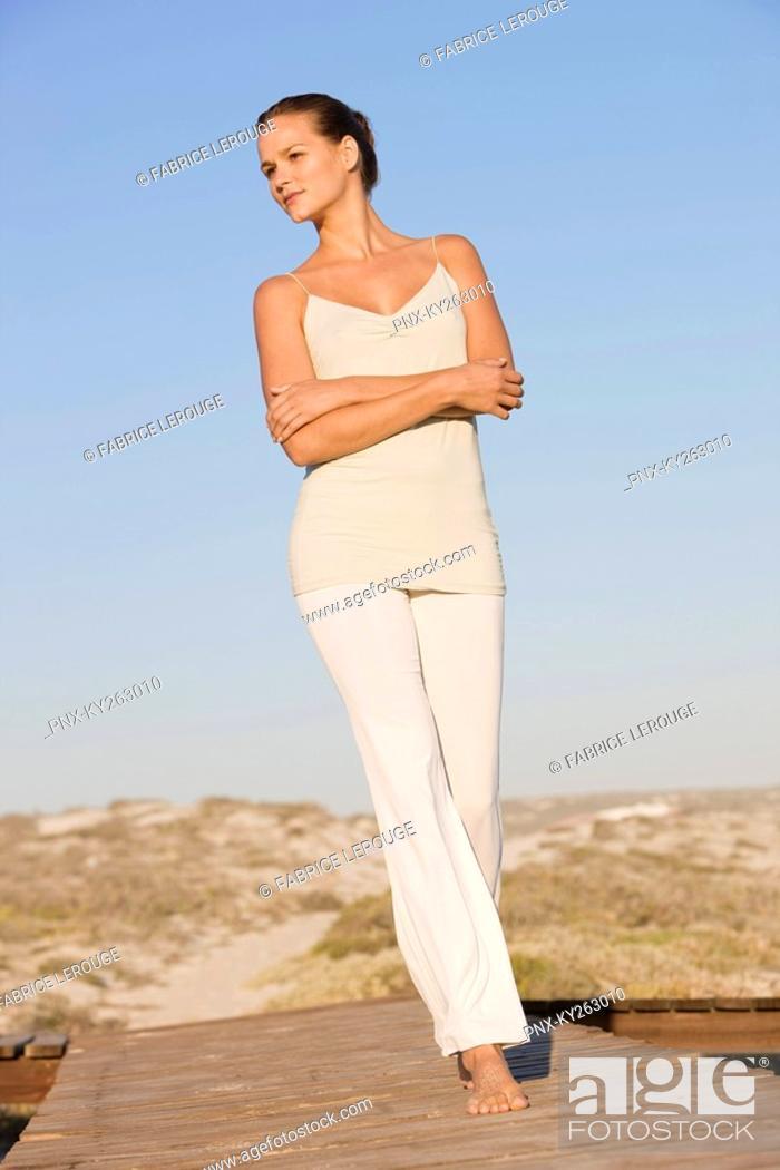 Stock Photo: Woman walking on a boardwalk.