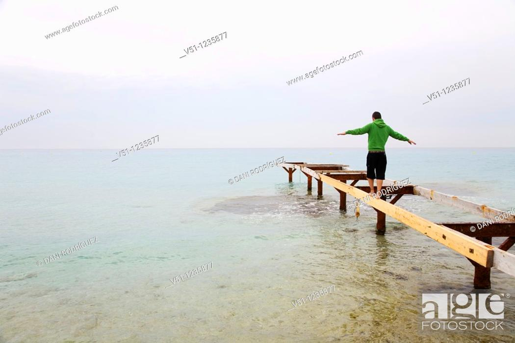 Stock Photo: Man doing balance in a pier in Formentera.