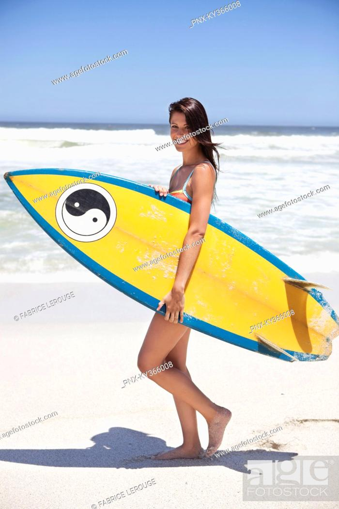 Stock Photo: Woman walking on the beach with surfboard.