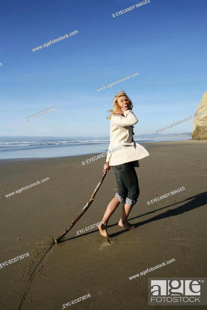 Stock Photo: Happy woman running on beach in winter.