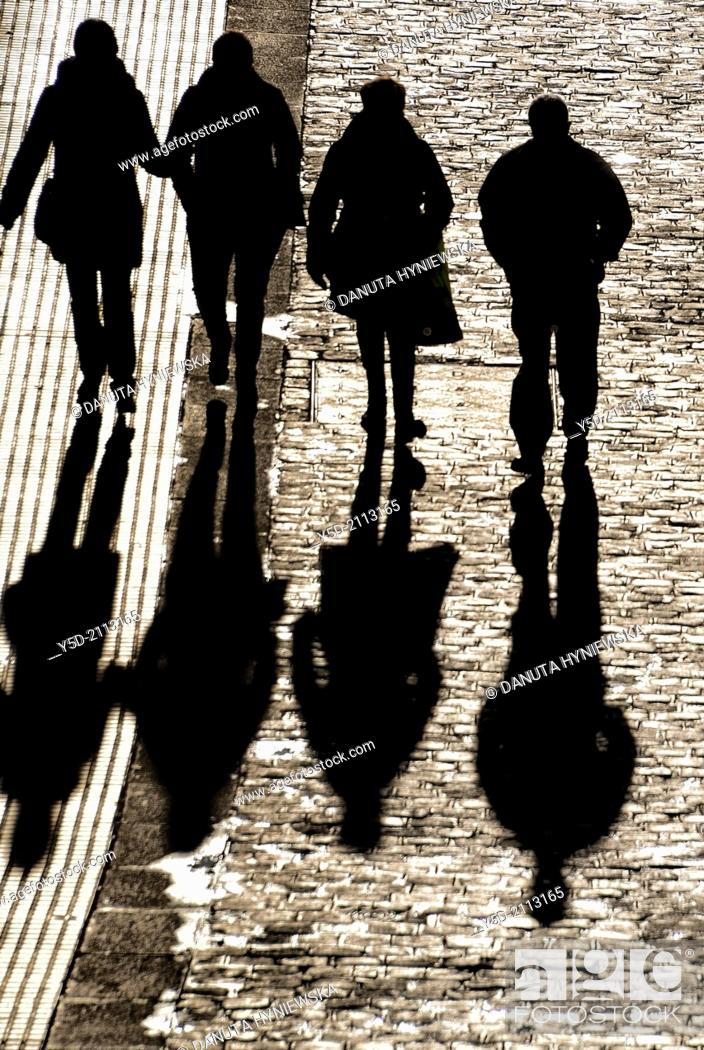 Stock Photo: people walking paved street with long shadows, view from above.