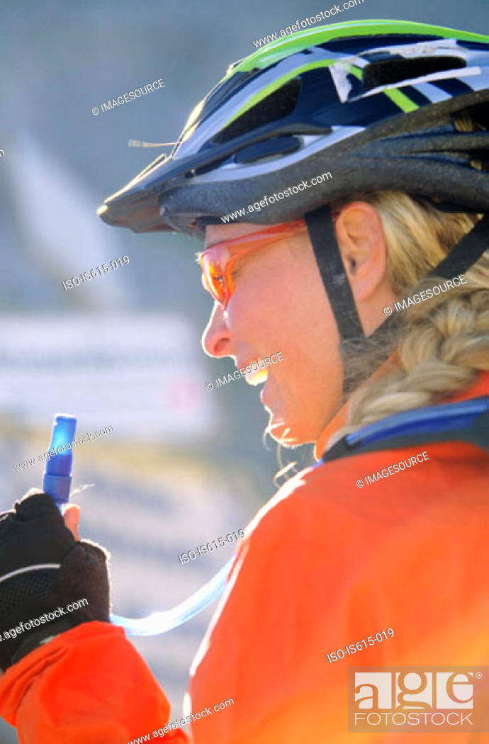 Stock Photo: Cyclist holding water nozzle.