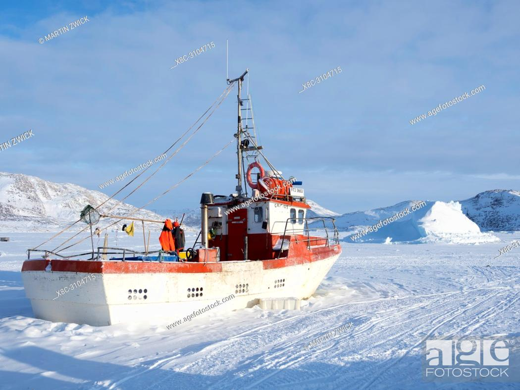 Stock Photo: The fishing village Ikerasak during winter in the Uummannaq fjordsystem north of the polar circle. Fishing boats in the frozen harbour.
