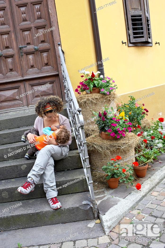 Stock Photo: Mother breastfeeding her daughter on a home staircase.