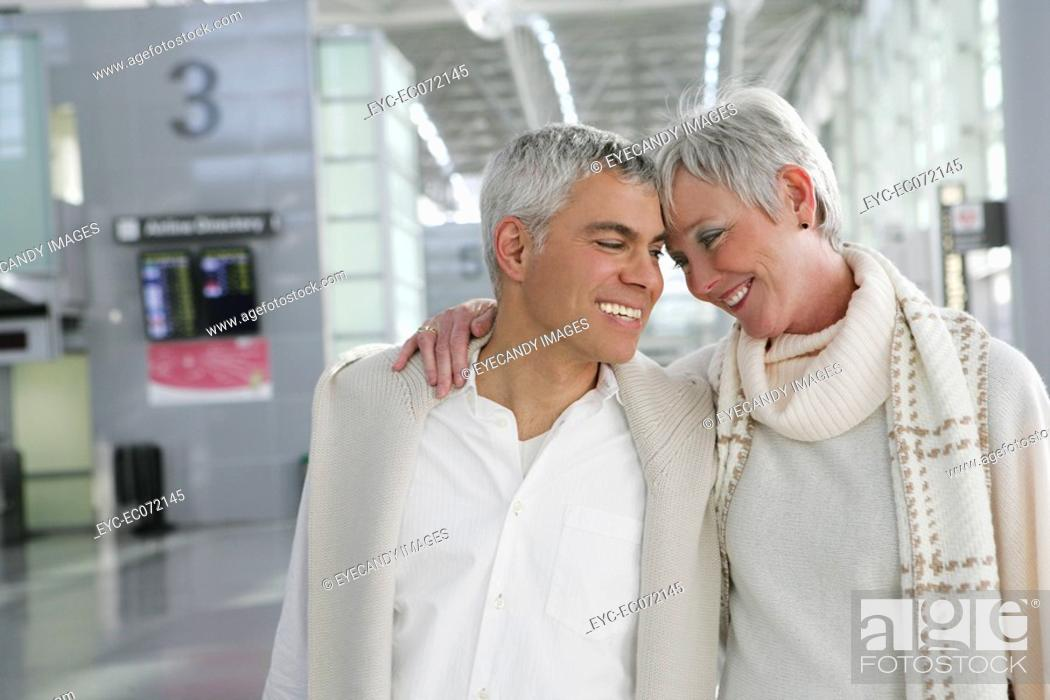 Stock Photo: Happy mature couple walking in airport.