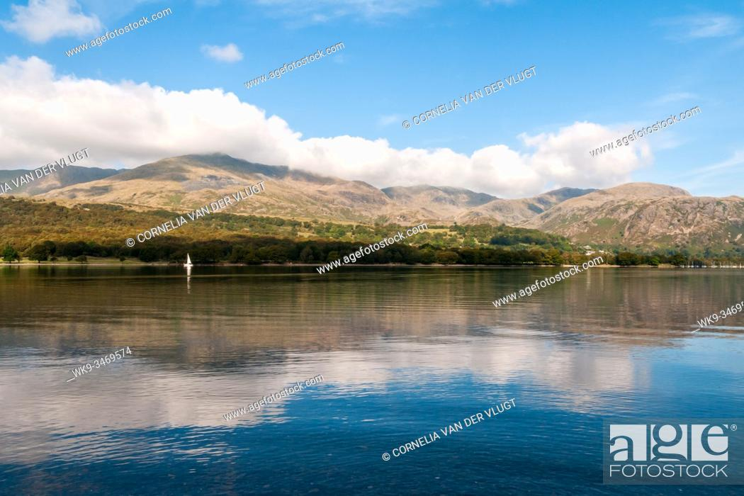 Stock Photo: Coniston Water in the Lake District in England on a beautiful quiet morning during early autumn. A single white sailing boat is on the horizon and the Coniston.