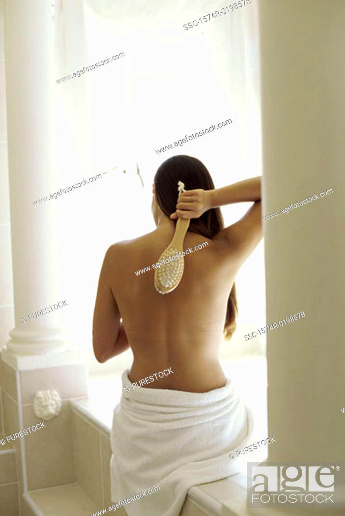 Stock Photo: Rear view of a young woman scrubbing her back with a brush.