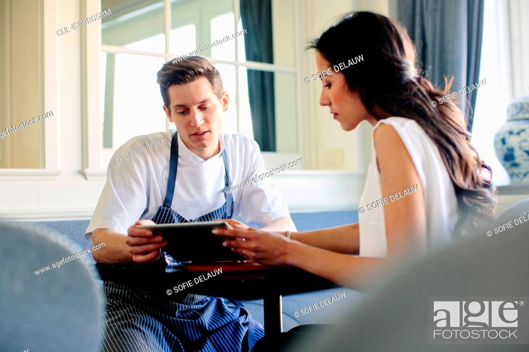 Stock Photo: Young male chef planning menu with female manager using digital tablet.