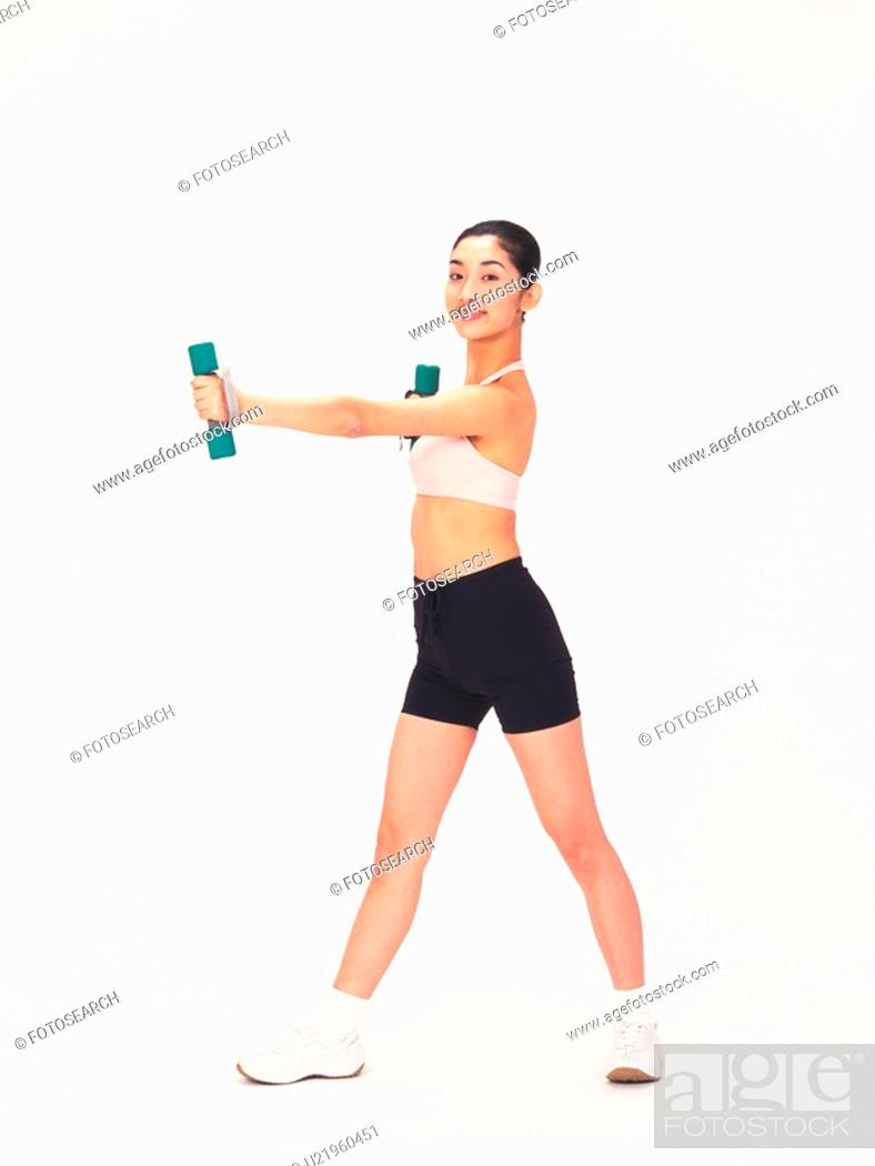 Photo de stock: Image of a Young Adult Woman Posing and Lifting Some Weights, Smiling, Looking at Camera, Side View.