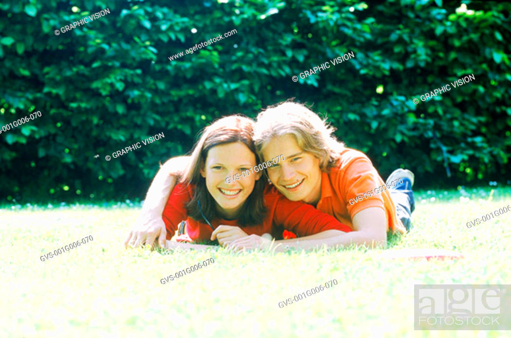 Stock Photo: Portrait of young couple lying on the grass.
