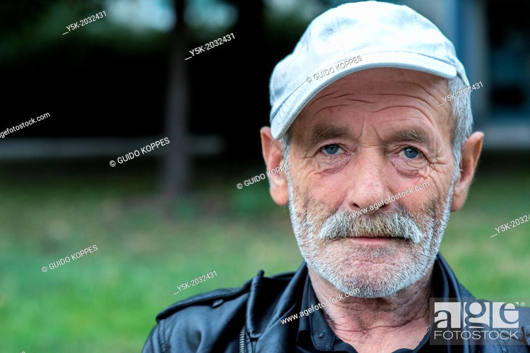 Stock Photo: Karl Marx Allee, East-Berlin, Berlin, Germany. Portrait of a senior adult man, spending his evening near a plantation in his neighborhood.
